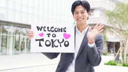 Young japanese man holding welcome message board.