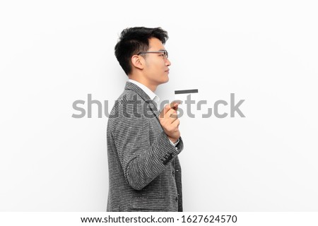 young japanese man on profile view looking to copy space ahead, thinking, imagining or daydreaming. credit card concept.