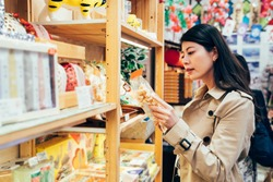 young japanese mom choosing snack for kids in local specialty shop in dotonbori osaka japan. asian mother buying food cookies for family after work in the vendor. beautiful lady reading the mark.