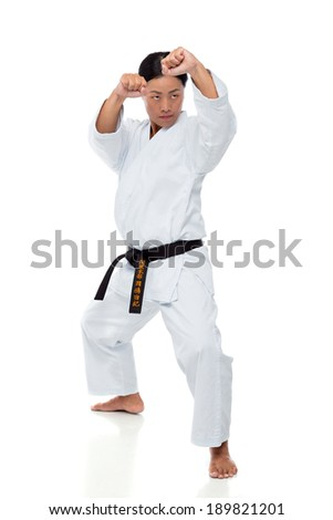 Young Japanese woman training karate isolated on white background