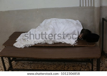 Young Jewish boy sleeps on a bench while covered with a white tablecloth after staying up late #1012306858