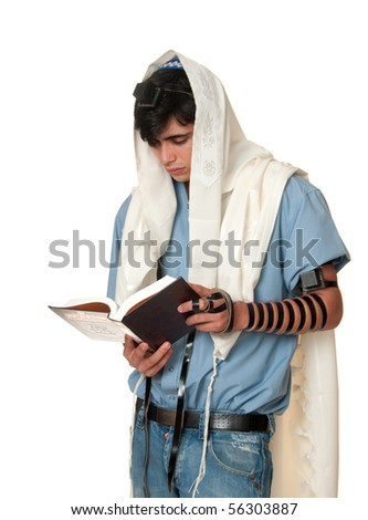 young Jewish man does morning prayers wearing a prayer shawl and phylacteries