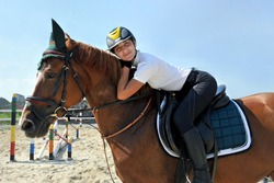 Young jockey girl riding bay horse on arena at equestrian school.