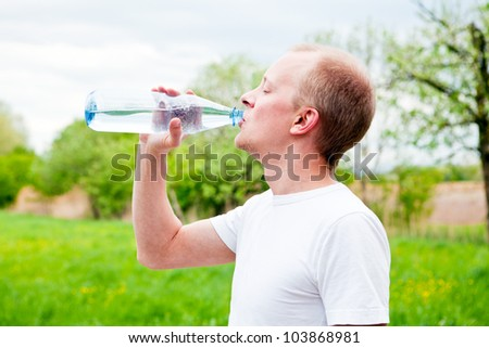 young jogger is drinking water outdoor