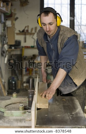 Young joiner making furniture in his manufactory.