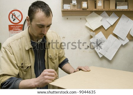 Young joiner making furniture in his manufactory