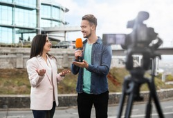 Young journalist interviewing businesswoman on city street
