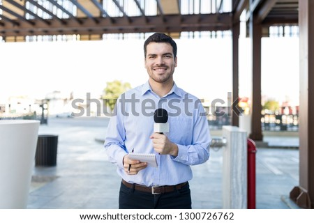 Young journalist looks confident before taking down another newscast
