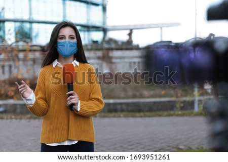 Young journalist with medical mask and microphone working on city street. Virus protection Сток-фото ©
