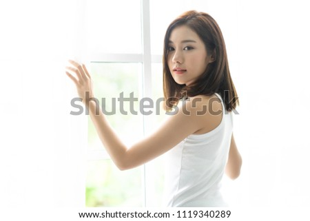 Young joyful Asian woman turn back and holding the curtains open to look out of large light window at home, turning to look and smile at camera. Beauty and Healthy Woman.