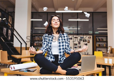 Young joyful brunette woman having meditation on table surround work stuff and flying papers. Cheerful mood, taking a break, at  work, studying, relaxation, smiling with closed eyes