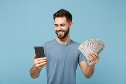 Young joyful man in casual clothes posing isolated on blue wall background, studio portrait. People lifestyle concept. Mock up copy space. Holding mobile phone, fan of cash money in dollar banknotes