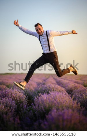 Young joyful man jumping up in lavender field in bloom