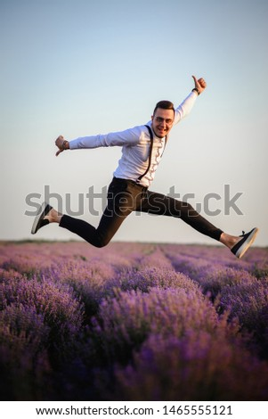 Young joyful man jumping up in lavender field in bloom, success concept