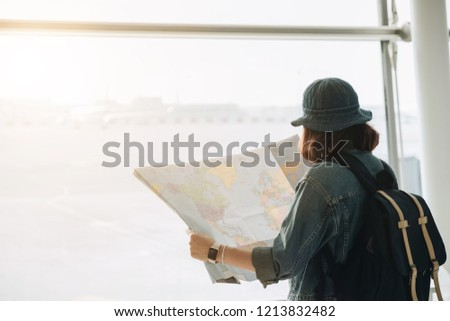 Young joyful traveler tourist woman with paper map, wait in lobby hall at airport. Passenger traveling abroad on weekend getaway. Air flight concept #1213832482