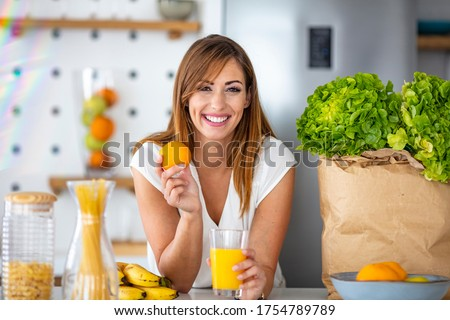 Young joyful woman drinking orange juice and standing near a kitchen table. Close up of a woman drinking juice in her kitchen. Fit smiling young woman preparing healthy fruit juice