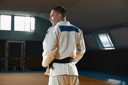 Young judo caucasian fighter in blue kimono with black belt posing confident in the gym, strong and healthy. Practicing martial arts fighting skills. Overcoming, reaching target, self building up.