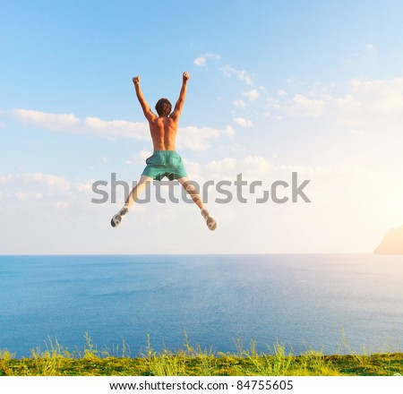 Young jumping man with sea and sky on the background