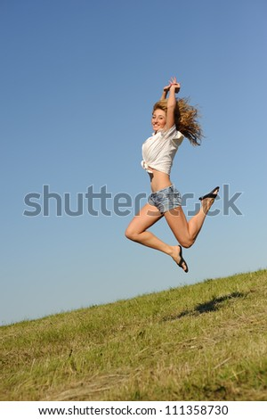 Young jumping woman on the green summer field
