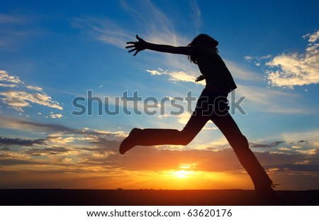 Young jumping woman with raised hands on sunset