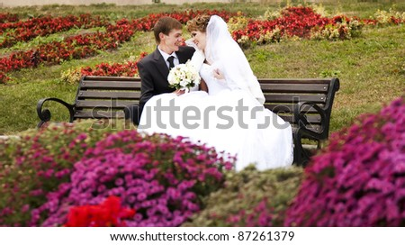 Young just married couple sitting close to each other on bench in park. - stock photo