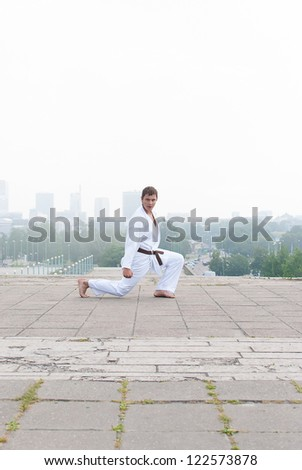 Young karate master doing exercise n the morning on city background Stock fotó ©
