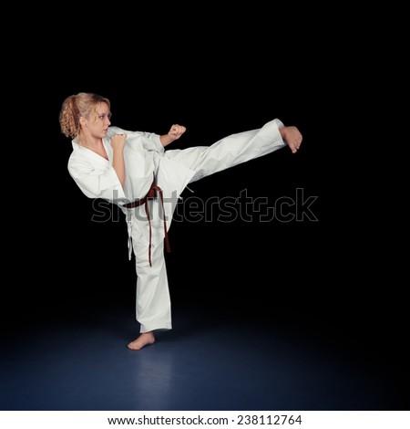 Young Karate Woman in a White Kimono Kicking - Portrait of a young beautiful martial arts girl in kimono exercising
