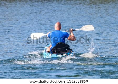 Young Kayaker Paddling Kayak. Sportsman kayaking Blue Water.