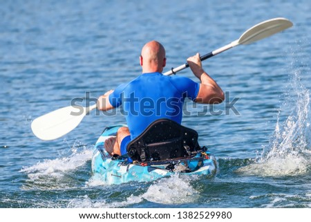 Young Kayaker Paddling Kayak. Sportsman kayaking Blue Water.