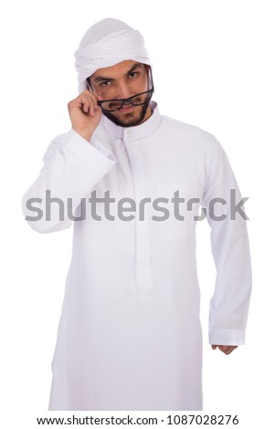 Young khaeeji man wearing thobe and headscarf moving the glasses he wears down and looking behind it, isolated on a white background. #1087028276