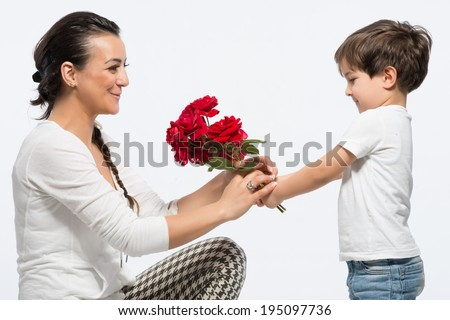 Young kid giving bouquet of red rose to his mom