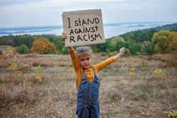 Young kid holding a poster with anti-racism message over beautiful nature background, activism and human rights movement, outdoor lifestyle
