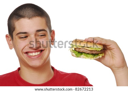 Young kid holding and eating a hamburger on white background.