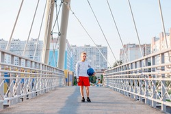 Young kid model wearing red shorts and white shirt holding the ball on the bridge