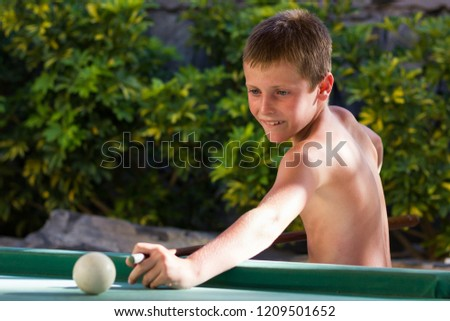 Young kid playing pool shirtless at resort recreation area. Blonde boy holding cue aiming white ball on billiards table. Summer hotel vacation, fun holidays, focus concepts #1209501652