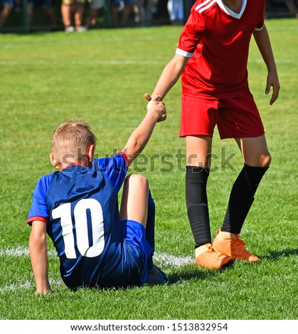 Young kid soccer player helps on the field