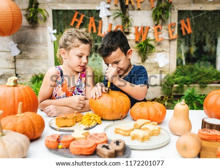 Young kids carving Halloween jack-o lanterns