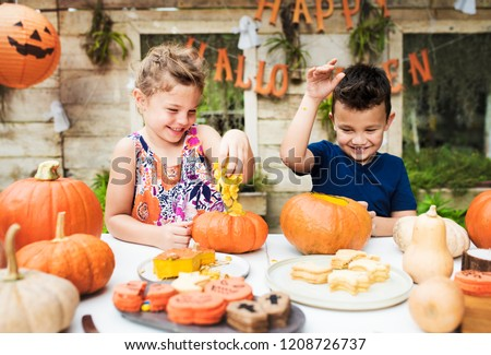 Young kids carving Halloween jack-o-lanterns