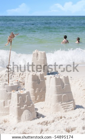 Young kids having fun in gorgeous ocean by sand castles