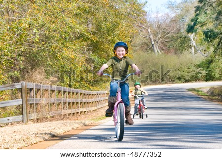 Young kids riding bikes on rural road