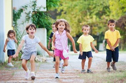 Young kids running together outdoors.