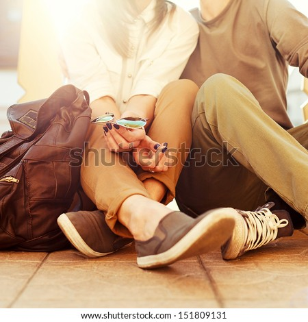 Young kissing happy couple in love sitting on the ground in summer sunny evening