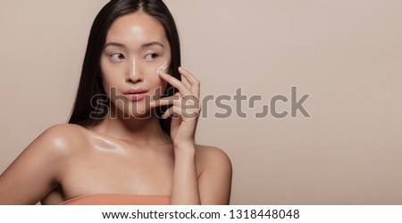 Young Korean woman applying moisturizer to her face over beige background. Young woman with cosmetic cream on a cheek and looking away.