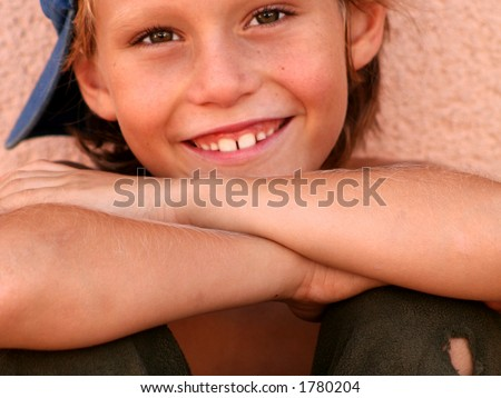 Young lad with cheeky grin and a hole in trousers