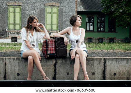 Young ladies with old suitcases on a platform
