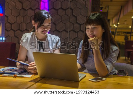Young ladies working overtime on laptop in co-working space office
