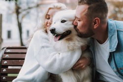 Young lady and man are resting on an alley bench, hugging and kissing white fluffy dog