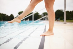 Young lady by the swimming pool, checking the water temperature with her feet, making water splashes.