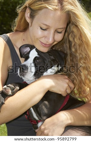 Young lady cuddles her Pit Bull puppy