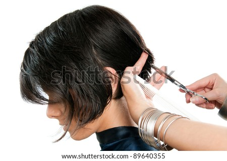 Young lady cutting hair at the hairdresser isolated on white background